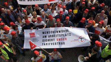 """Streik-Versammlung mit Transparenten """"Wir streiken"""" und """"Menschenwürde am Arbeitsplatz sichert unser Tarifvertrag""""."""