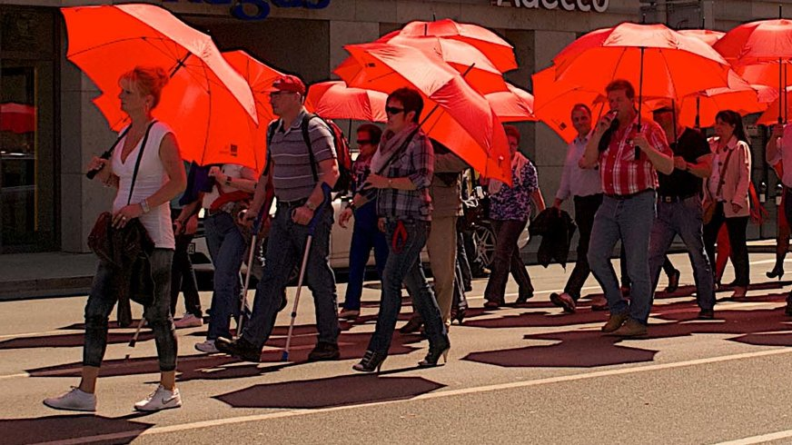 Langer Zug von Menschen mit roten Schirmen.