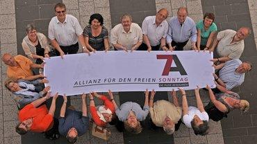 """Menschen halten ein Plakat """"Allianz für den freien Sonntag"""" –aus der Vogelperspektive."""