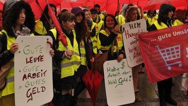 """Demonstration mit roten Schirmen und Schildern, z. B. """"Habe Arbeit, aber kein Geld""""."""