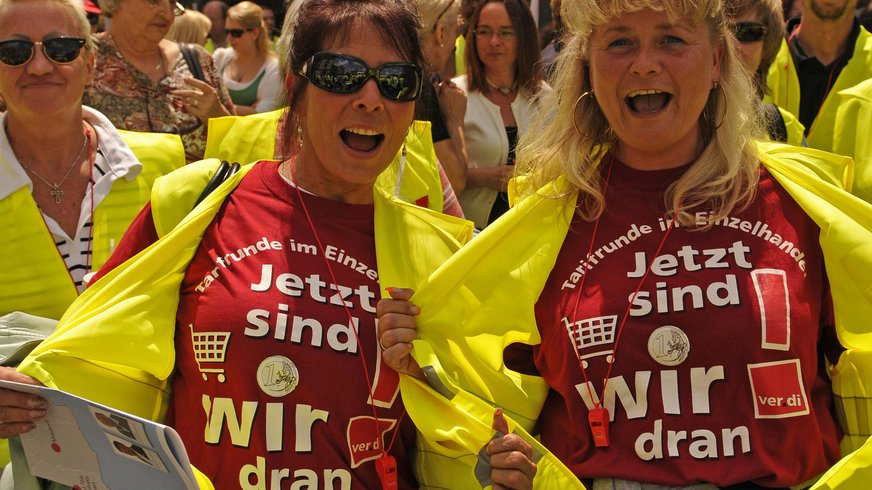 """Skandierende Frauen mit ver.di-Warnwesten und T-Shirts """"Jetzt sind wir dran""""."""