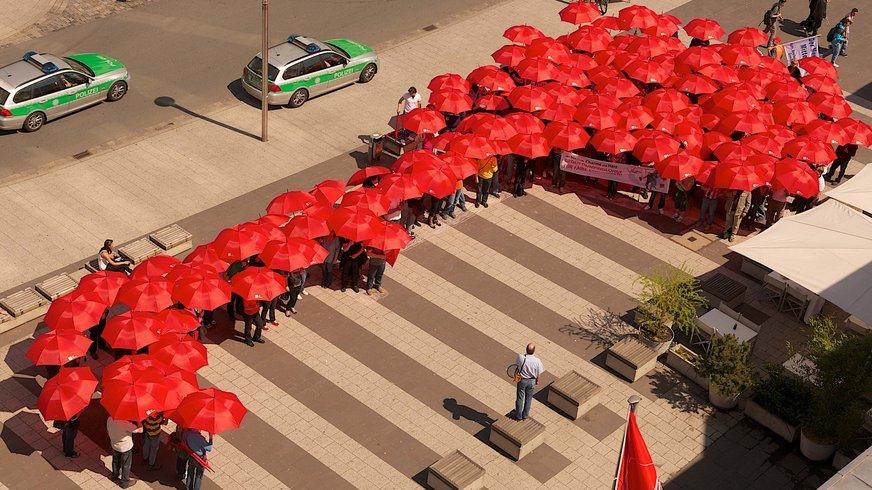 Menschen mit roten Schirmen aus der Vogelperspektive.