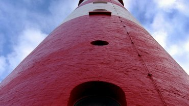 Rotweißer Leuchtturm aus der Froschperspektive.