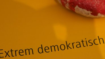 """Schriftzug """"Extrem demokratisch"""" auf einem Flugblatt."""